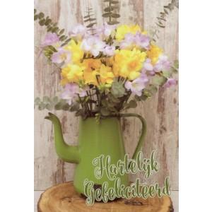 Wenskaart hartelijk gefeliciteerd met een mooie bos bloemen in een groene schenkkan