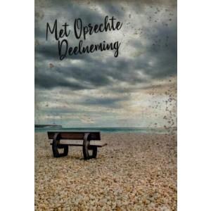 Condoleance wenskaart in kleur met een afbeelding van een bankje op het strand aan de kust.