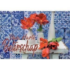 Wenskaart van harte beterschap met rode bloemen op een wit tafeltje